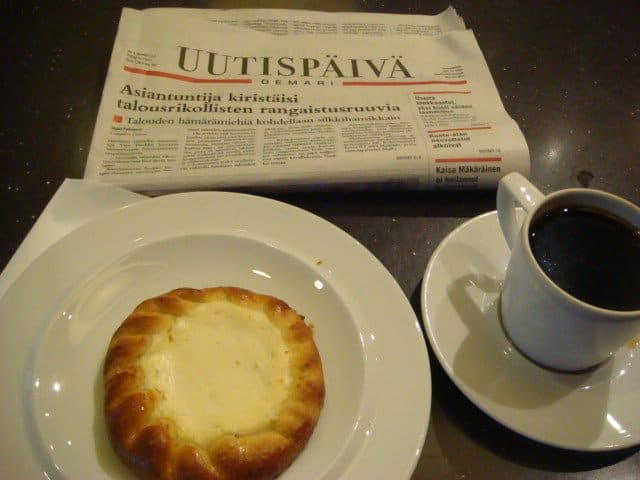 Angela with Finnish newspaper and coffee